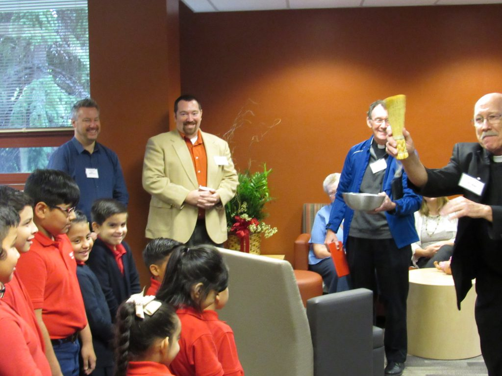 Rev. Rick Abert, S.J. blesses one of the renovated rooms in the school.